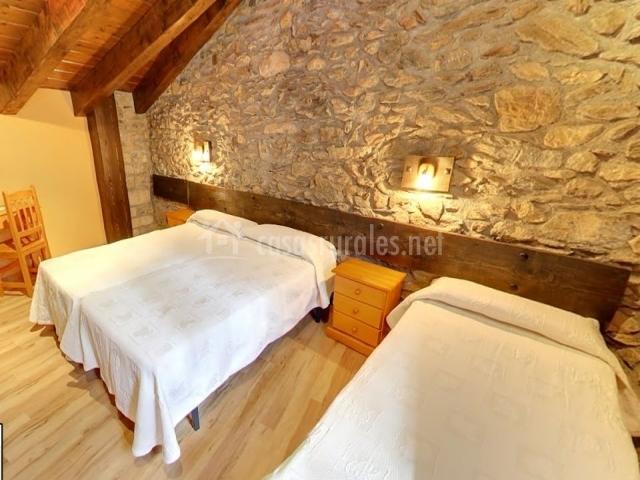 Dormitorio triple con 3 camas y pared de piedra