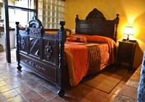 Dormitorio de matrimonio con colchas naranjas