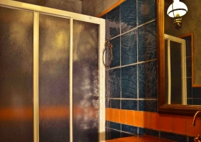 Bañera y mueble de madera. Azulejos azules