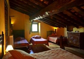 Vista de las camas del dormitorio con techo de madera abuhardillado