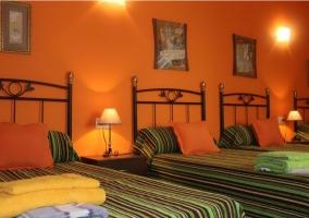 Habitación naranja con 4 camas