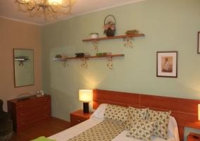 Habitación verde con cama de matrimonio y cómoda