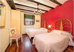 Dormitorio doble con pared en rojo y vigas de madera en el techo