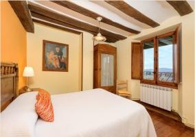 Habitación con cama de matrimonio y suelos y techos de madera