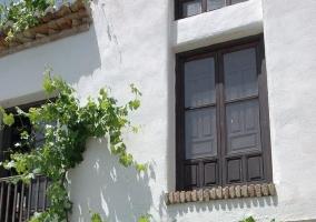 Comedor con mesa de madera y ventana acristalada que se puede abrir para unirse al patio