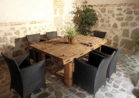Mesa de madera y butacas en el patio