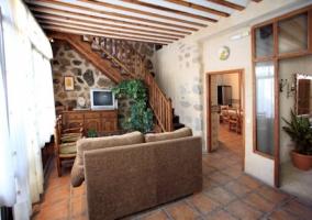 Sala de estar con escaleras al primer piso y televisor