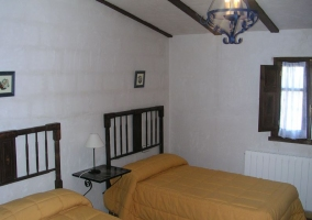 Dormitorio doble con vigas y cabeceros de madera