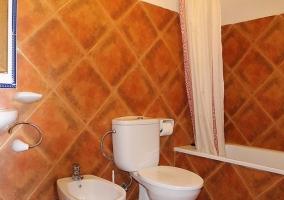 Habitación doble con cama de matrimonio que cuenta con colcha naranja