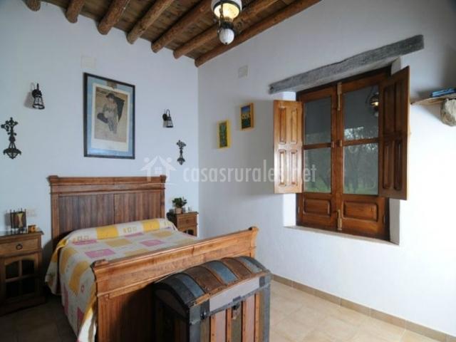 Habitación doble con cama de matrimonio y baúl de madera antiguo