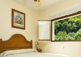 Cama de matrimonio en habitación con ventana amplia