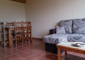 Sala de estar con el sofá cama y techo de madera