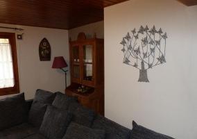 Sala de estar con televisor colgado en pared de piedra
