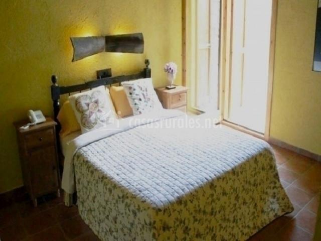 Habitación doble con cama de matrimonio y pared amarilla