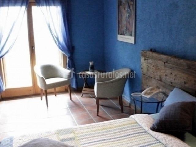 mesita y sillones en dormitorio doble