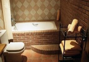 Bañera rodeada de ladrillos en habitación