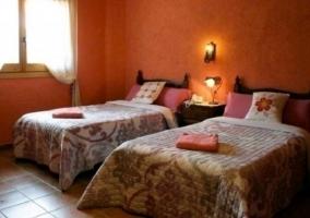 Dos camas individuales en habitación de color salmón