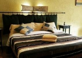 Otra de las habitaciones con cama amplia y colcha verde