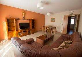 Salón en tonos naranja con sofá en chocolate