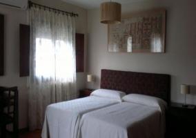Dormitorio con dos camas blancas y armario