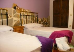 Dormitorio con camas individuales y pared en morado
