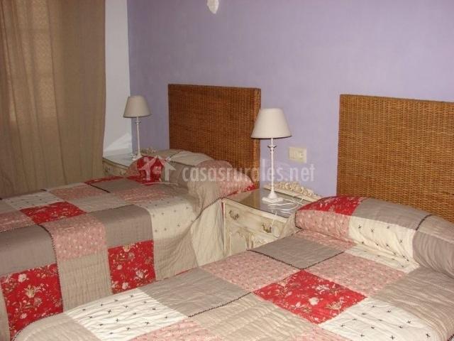 Dormitorio doble con camas individuales y cabeceros de mimbre