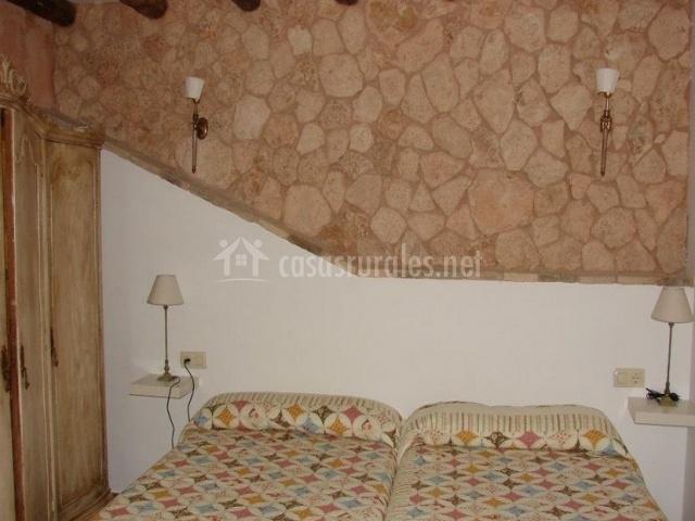 Dormitorio doble con camas individuales y pared de piedra