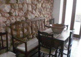 Comedor con muro de piedra y cristalera