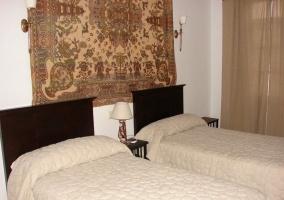 Dormitorio doble con camas individuales y colchas blancas
