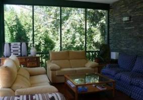Sala de estar con grandes cristaleras y televisor