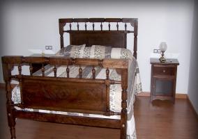 Cama de matrimonio con cabecero de madera y mesita de noche