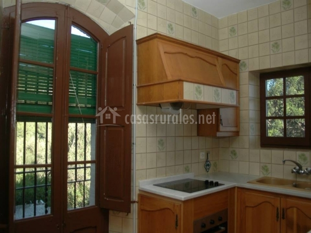 Cocina con gran ventanal y muebles de madera