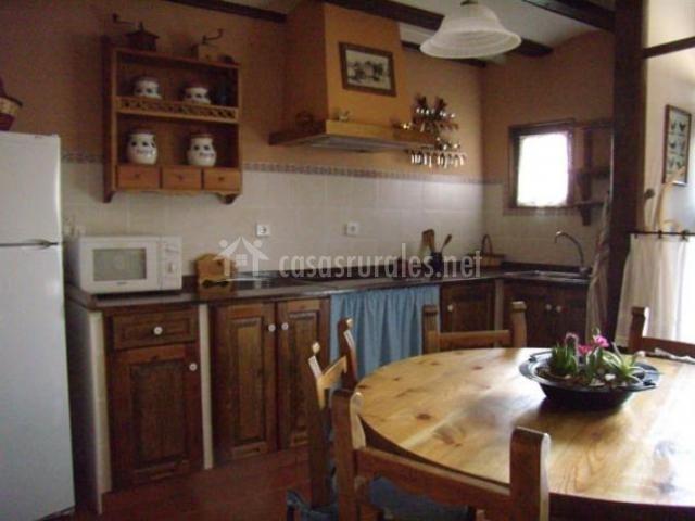 Cocina con electrodomésticos blancos y mesa de comedor redonda de madera