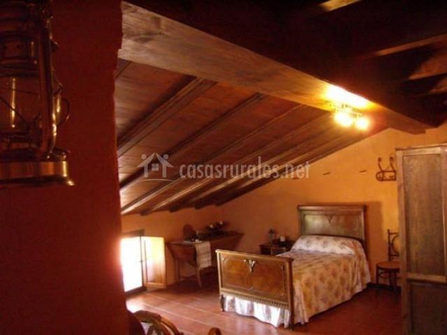 Habitación abuhardillada con cama individual y vigas de madera en el techo