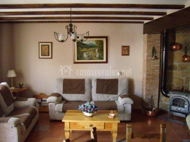 Salón con dos sofás grises y chimenea de leña
