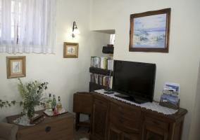 Sala de estar con televisor y estante con libros