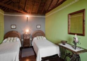 Dormitorio doble con un par de camas y techo de madera