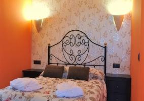 Dormitorio de matrimonio con pared florida y naranja