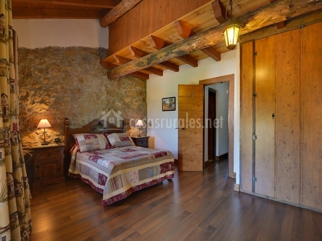 Dormitorio de matrimonio con muro de piedra y vigas de madera