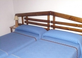 Habitación con dos camas y cabeceros de madera
