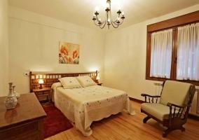Habitación con cama de matrimonio y butaca