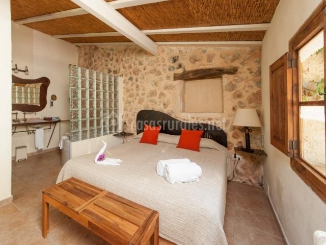 Dormitorio suite especial con pared de piedras