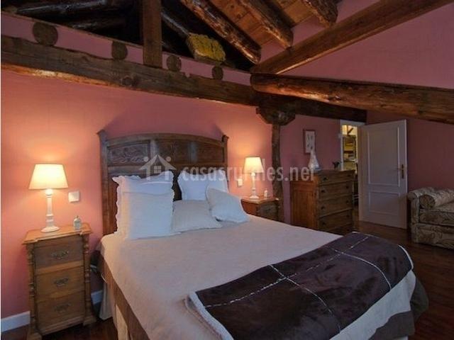 Habitación con cama de matrimonio y vigas en el techo