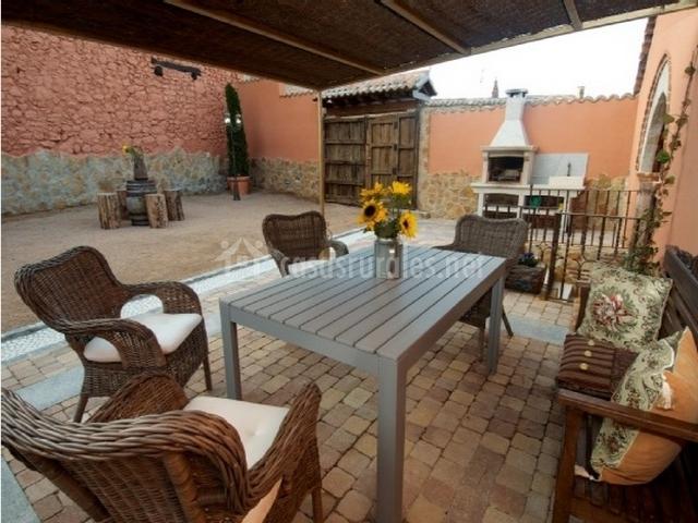 Porche con mesa, sillas de mimbre y bancos de madera