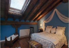 Habitación abohardillada con cama de matrimonio y mosquitera