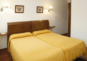 Dormitorio doble con colchas en amarillo y cabeceros de madera