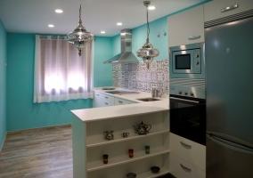 Cocina con paredes azules y encimera en L