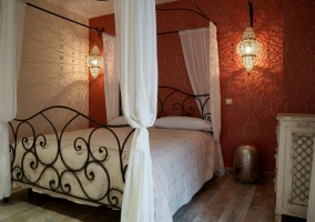 Dormitorio con cama de matrimonio con dosel