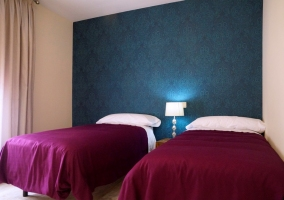 Dormitorio con dos camas y pared azul