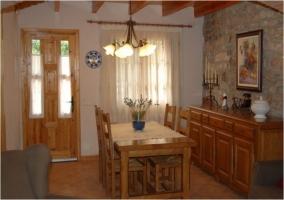 Comedor con mesa de madera y sillas en el salón de la casa rural